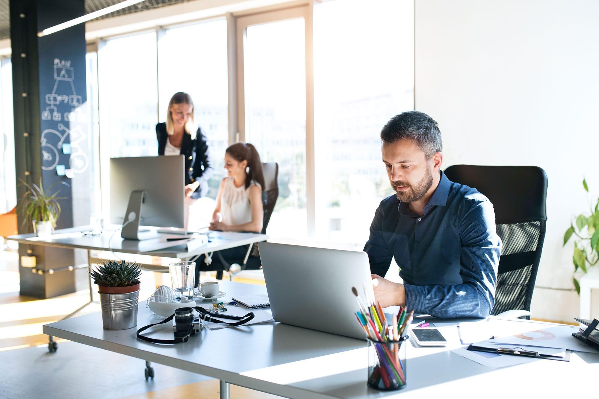 man-sat-at-desk-infront-of-laptop